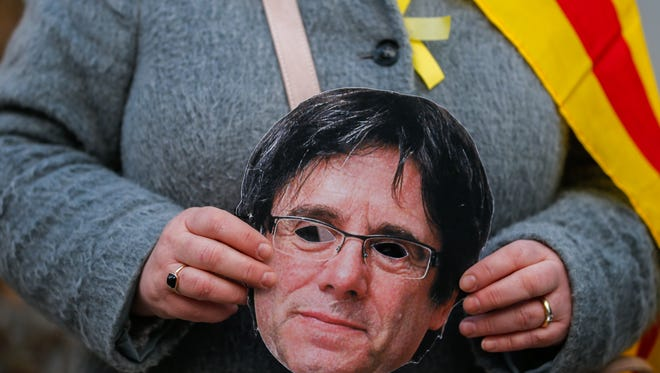 A demonstrator holds a mask of detained former Catalan leader, Carles Puigdemont, near the Cologne Cathedral in Cologne, Germany, March 26, 2018.