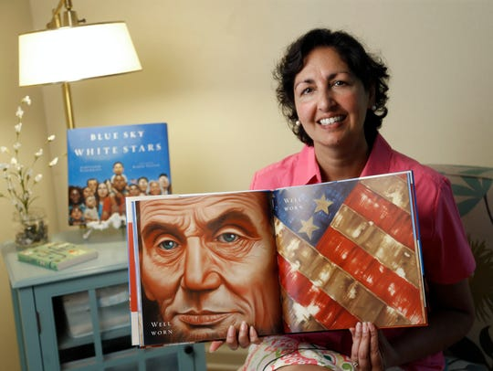 Sarvinder Naberhaus of Ames holds a copy of her book,