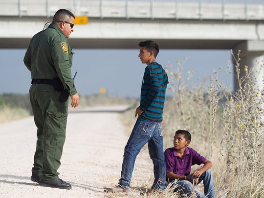 Two young unaccompanied Honduran boys turn themselves in to a Border Patrol agent near the Anzalduas International Bridge not far from the Rio Grande in Mission, Texas, on Saturday, June 21. The boys walked down a dirt road coming from the Rio Grande, sat down at the end of the road and waited until they turned themselves in to the agent.