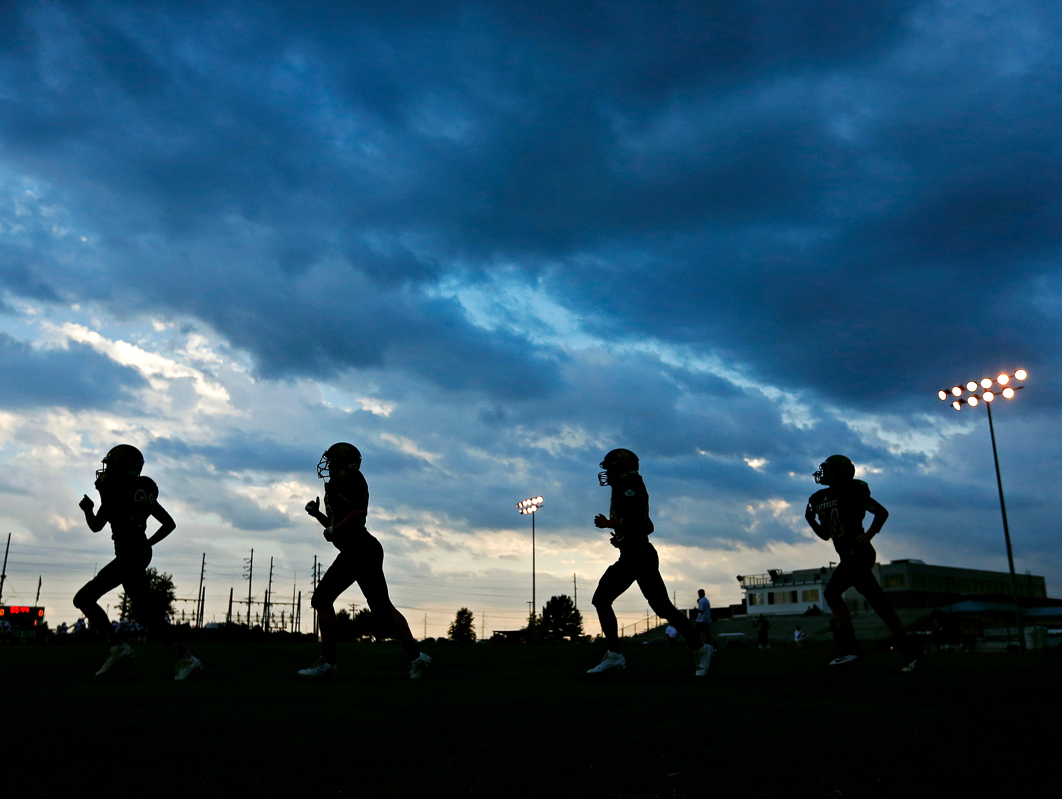 Springfield Catholic players jog during warm ups prior to the game between Springfield Catholic High School and Fair Grove High School at Springfield Catholic High School in Springfield, Mo. on Sept. 9, 2016. The game was postponed due to severe weather in the area.