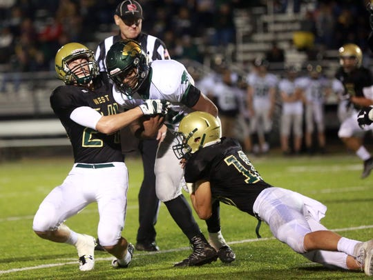 West High's Austin West, left, and Cole Mabry tackle