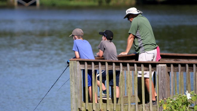 Mike Weeks, right, takes his grandsons, Braxton, left, and Braden Meador fishing at Wells Lake, Friday, July 24, 2020, during their weekend visit to Fort Smith. Braxton, 10, and Braden, 12, are the sons of Heather and Brad Meador of Springdale.