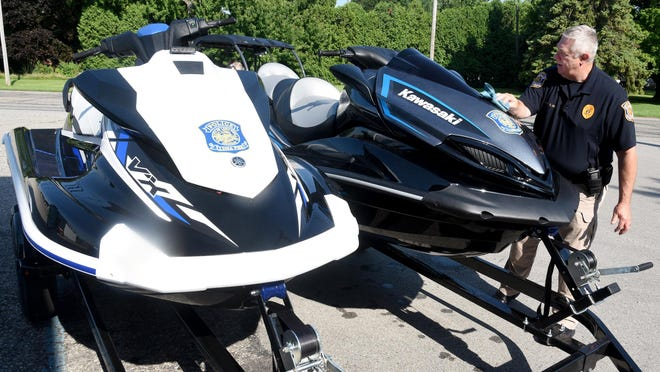 City of Luna Pier Police Chief Brett Ansel cleans jet skis that are part of the department's marine unit. Earlier this month, city residents rejected the renewal of a millage used to fund the department.