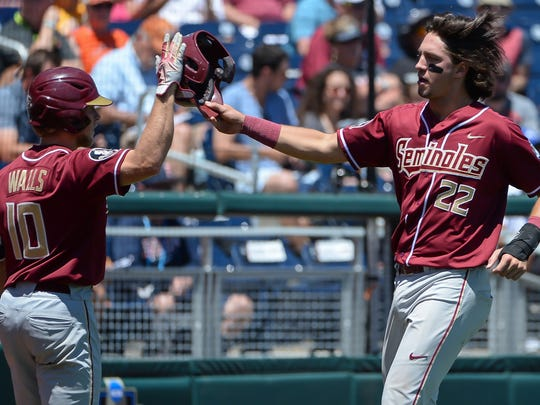 Florida State infielder Drew Mendoza (22) celebrates with Taylor Walls (10) after scoring in the second inning against Cal State Fullerton at TD Ameritrade Park in Omaha.