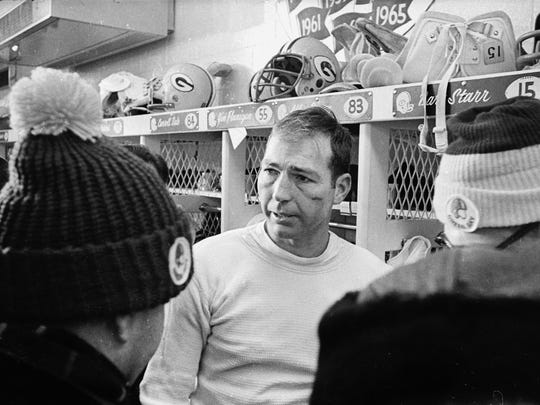 Packers quarterback Bart Starr, his face swollen from the cold, talks to reporters at his locker after Green Bay's victory in the Ice Bowl.