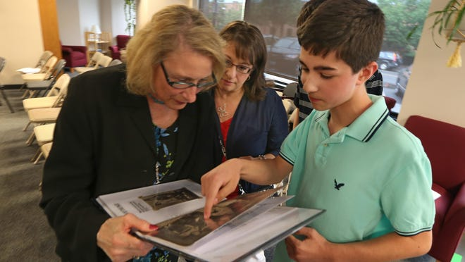 Michael Salamone, 14, of Greece, explains a family photo as he shows his Italian heritage project to OSIA trustee Marjorie Focarazzo of Rochester at the monthly meeting of the Order Sons of Italy in America, Vince Lombardi Lodge 2270, held this month in East Rochester. Looking on is Michael's mother, Mary Salamone. Michael won first place for eighth-graders in an essay contest put on by the organization.