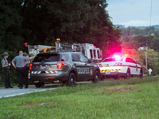 Pennsylvania State Troopers gather at their car while investagating the scene of a fatal one-car crash on Cranberry Rd., in Tyrone Township, Sunday, July 23, 2017.