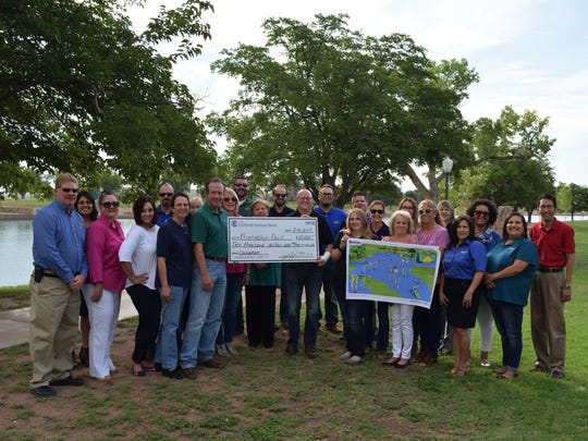 Members of Carlsbad National Bank gather during a check presentation benefiting Friendship Park.