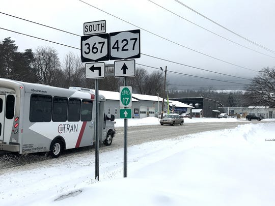 Vehicles drive on snow-covered streets Wednesday afternoon in the Village of Wellsburg.