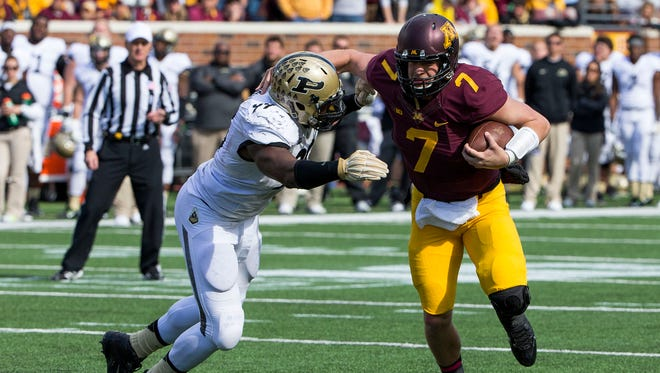 Minnesota Golden Gophers quarterback Mitch Leidner (7) rushes with the ball as Purdue Boilermakers defensive end Ryan Russell (99) attempts to make a tackle in the second half at TCF Bank Stadium.