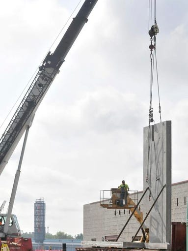 A crane lifts a wall section as workers place the section of the St. Clair County Convention Center Thursday, Aug. 21 next to the Doubletree by Hilton in Port Huron.