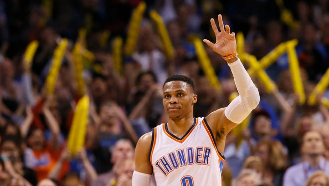 Oklahoma City Thunder guard Russell Westbrook waves to the crowd after accomplishing his 41st tri-ple-double, tying an NBA record.