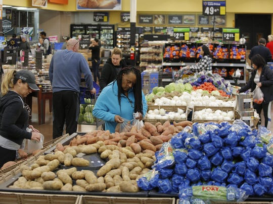 """FILE - In this Nov. 27, 2019, file photo people shop for food the day before the Thanksgiving holiday at a Walmart Supercenter in Las Vegas. If you've been guilty of throwing away groceries that have gone bad, you're probably not shopping as efficiently as you could. """"Try eating your way through some of your food,"""" says Natasha Knox, a member of the Financial Therapy Association's board of directors and founder of Pax Planning. (AP Photo/John Locher, File)"""