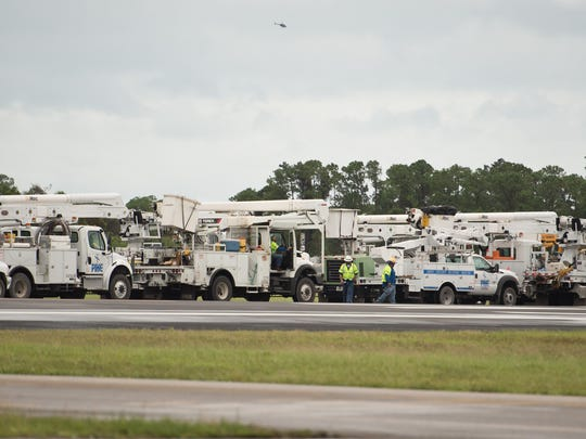 Dozens of utility trucks, many from out of state,