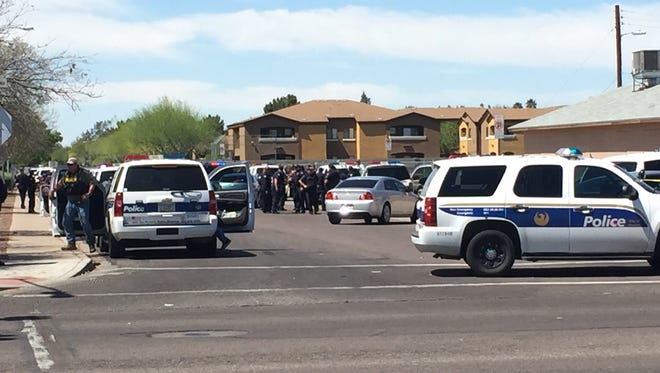 Dozens of Phoenix police officers stand ready to enter the apartment complex in the background.