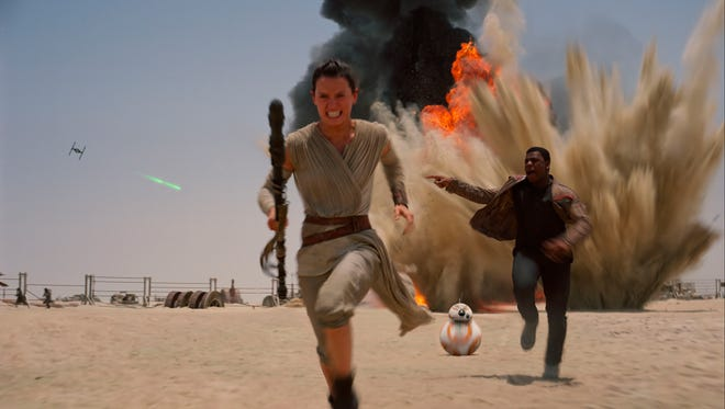 """Daisey Ridley as Rey, left, and John Boyega as Finn, in a scene from the new film, """"Star Wars: The Force Awakens,"""" directed by J.J. Abrams. The Disney movie releases in the U.S. on Dec. 18, 2015."""
