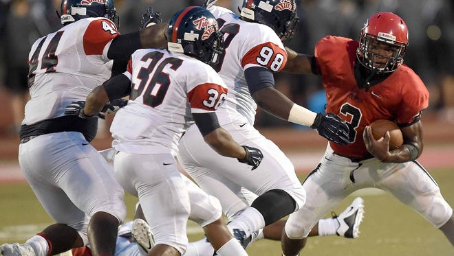 Clinton quarterback Cam Akers tries to find a way past three South Panola defenders in the opening game of the 2015 high school football season at Clinton High School on Thursday, August 20, 2015, in Clinton, Miss.