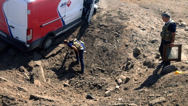 Turkish investigators search the site after a police minibus was destroyed in a bomb attack on Sept. 8, 2015, in Igdir. Fourteen Turkish police officers were killed in a bomb attack in eastern Turkey blamed on the outlawed Kurdistan Workers' Party (PKK), the official Anatolia news agency said.