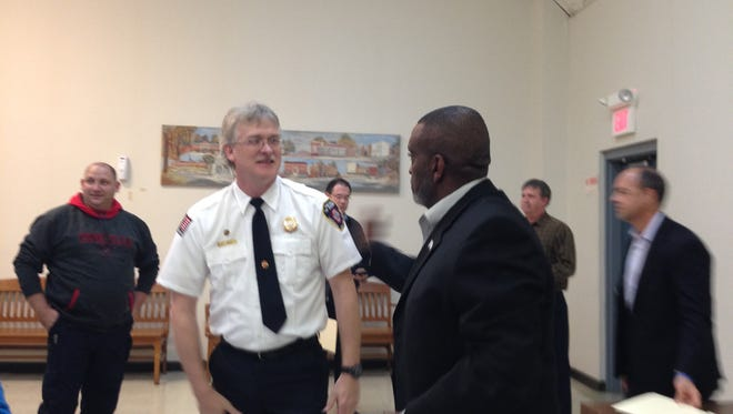 Pineville Mayor Clarence Fields (right) congratulations new Pineville Fire Department Chief Scott Kessler on Tuesday night after Kessler's appointment was made official by a unanimous vote.