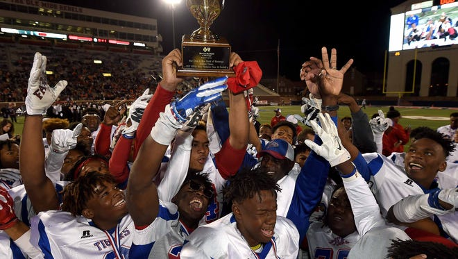 The Noxubee County Tigers celebrate with the trophy after beating St. Stanislaus for the second consecutive year in the MHSAA Class 4A championship. Noxubee won 44-23.