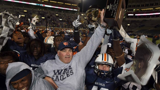 Wayne County head coach Todd Mangum and the War Eagles celebrate with the trophy after a dramatic 45-41 victory over Oxford on Saturday, December 5, 2015, in the MHSAA Class 5A State Football Championship in Vaught-Hemmingway Stadium on the Ole Miss  campus in Oxford, Miss.