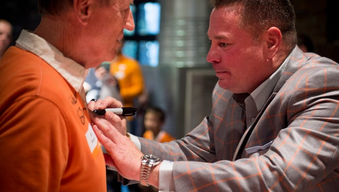 Tennessee football coach Butch Jones, right, signs a shirt for Joe Wilson of Dickson during the UT Caravan stop at The Factory, Tuesday, May 10, 2016, in Franklin, Tenn.