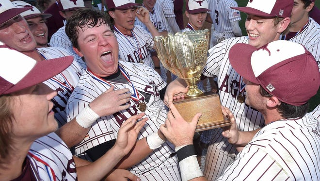 The Kossuth Aggies celebrate their Class 3A state title with the gold glove trophy after beating St. Andrew's 7-1 on Friday.