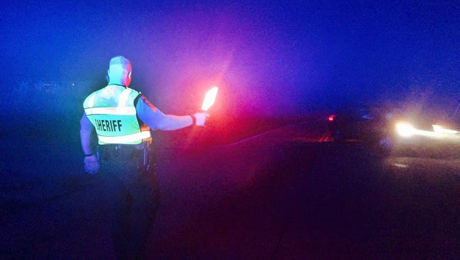 Sumner Deputy Steve Stewart redirects traffic away from the shootout crime scene on Highway 25 in Cottontown on Wednesday, June 15, 2016.