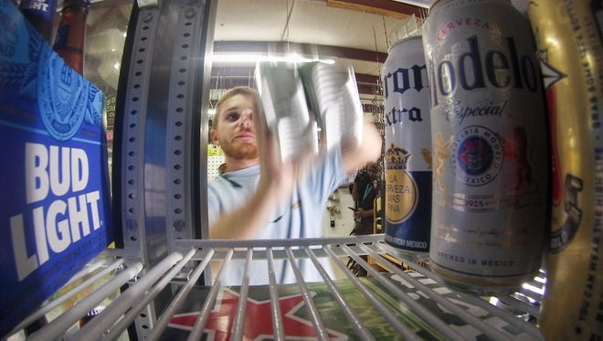 Gulf Breeze Bait and Tackle employee Alex Pilot stocks beer in a refrigerator at the store in Gulf Breeze on Wednesday, September 7, 2016.  The Gulf Breeze City Council is considering relaxing the hours during which alcohol may be sold.  Businesses like the Bait and Tackle shop which are open 24 hours a day could benefit if this passes.