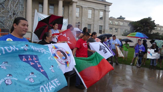 "Protesters brave rain Thursday to speak against the construction of the $3.8 billion Dakota Access pipeline. Nearly 100 people gathered outside the Old Capitol on the University of Iowa campus for the ""Nebi Bematesieni"" rally. The phrase means"" water is life"" in the Meskwaki language."