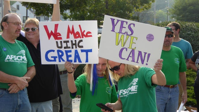 "Protesters from AFSCME hold signs reading ""We make UIHC great"" and ""Yes we can"" during a rally Friday outside University of Iowa Hospitals and Clinics. The rally, organized by SEIU, focused on nurse staffing concerns at the Iowa City-based hospital."