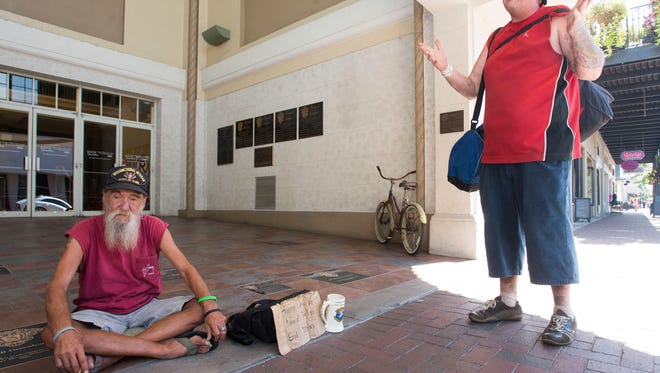 Homeless veteran, Buddy Capel, sits silently outside the Sanger Theatre in downtown and talks with fellow homeless man, Charles McClellan Wednesday afternoon. Capel has been on the streets for 14-months.