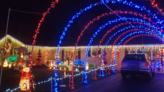 Marie Urich parks her car under a patriotic tunnel of lights that is part of a huge Christmas lights display in Warrington Township.