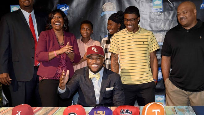 Cam Akers does the tomahawk chop after putting on a Florida State cap announcing his college decision as his family applauds behind him on Tuesday at the Mississippi Sports Hall of Fame and Museum in Jackson.