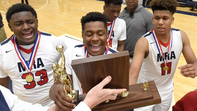 The MRA Patriots celebrate with the trophy after their 63-60 overtime win against Hillcrest on Saturday, February, 25, 2017, in the MAIS AAAA state basketball championship at Jackson Academy in Jackson, Miss.
