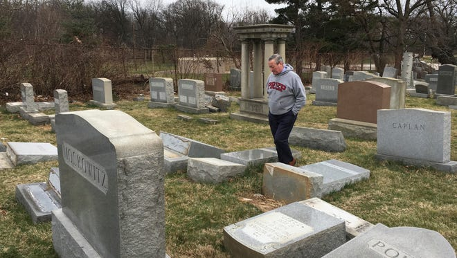 """Philadelphia Mayor Jim Kenney surveys the damage at Mount Carmel Cemetery, Monday, Feb. 27, 2017, in Philadelphia. Police investigated what they called an """"abominable crime"""" after several hundred headstones were damaged during the weekend at the Jewish cemetery dating to the late 1800s, said Steven Rosenberg, chief marketing officer of the Jewish Federation of Greater Philadelphia. (David Swanson/The Philadelphia Inquirer via AP)"""