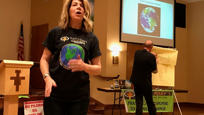 Jackie Schramm, director of St. Mary's Parish's Social Justice Ministry in Pompton Lakes leads a group discussion at an environmental event. Volunteer Norbert Langer takes notes in the background.