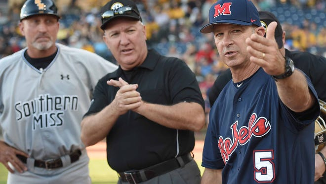 Ole Miss head coach Mike Bianco (5) meets with the umpires and Southern Miss head coach Scott Berry (40) before the game on Tuesday, April 4, 2017.
