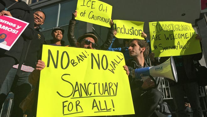 Protesters hold up signs outside a courthouse where a federal judge will hear arguments in the first lawsuit challenging President Donald Trump's executive order to withhold funding from communities that limit cooperation with immigration authorities Friday, April 14, 2017, in San Francisco.