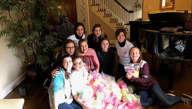 Taking a break from packing supplies for the Sister to Sister Period project are Girl Scouts and mentors, from left, Louise Adillon, Julia Needleman and Sydney Kuehn, bottom row;  Abbey Wish, Ruby Pollack, Caroline Davis and mentor Jamy Barton,  middle row; mentor Amy Dietrich and Rachel Solomon, top row. Jamy and Amy are sisters who started a similar program called 28 Days. They were the girls' inspiration for our Sister to Sister Period project and have mentored them on the project.