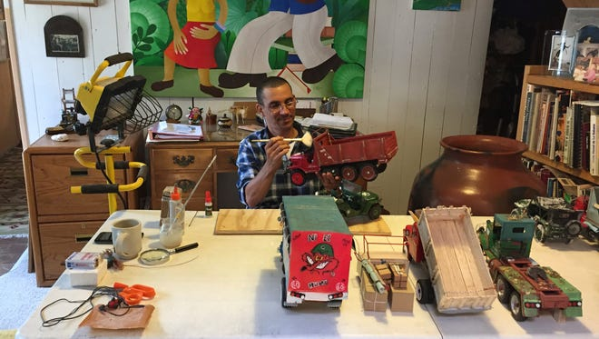 In this Sunday, July 9, 2017 photo Leandro Gomez Quintero, 40, of Baracoa, Cuba, prepares his artwork, in Santa Fe, N.M., for sale at the International Folk Art Market. Organizers of the market say shifting U.S. policies on security and immigration have not hampered participation by artists from 53 countries, from Cuba to Jordan. In its 14th year, the annual bazaar is expanding its mission to highlight innovation and high-fashion within folk art traditions. (Peggy Gusted via AP)