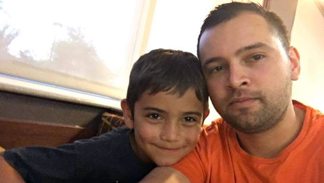 Acis Raiden Garcia, 8, of Phoenix and his father, Julio Garcia, survived a flash flood that killed 10 other family members July 15, 2017, in Payson, Ariz.