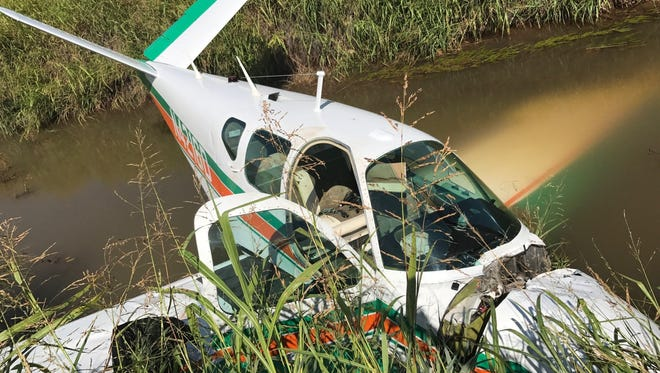 A small civilian airplane lies partially submerged Monday morning after it crash landed in an irrigation canal near Wichita Valley Airport. The pilot was transported to a Wichita Falls hospital for treatment.
