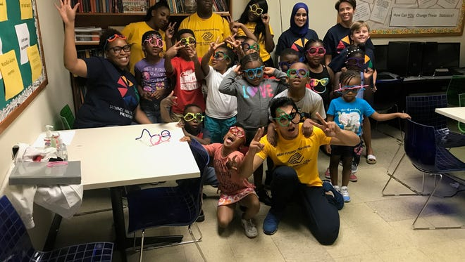 Health Fair participants show off theirpipe cleaner eyeglasses.