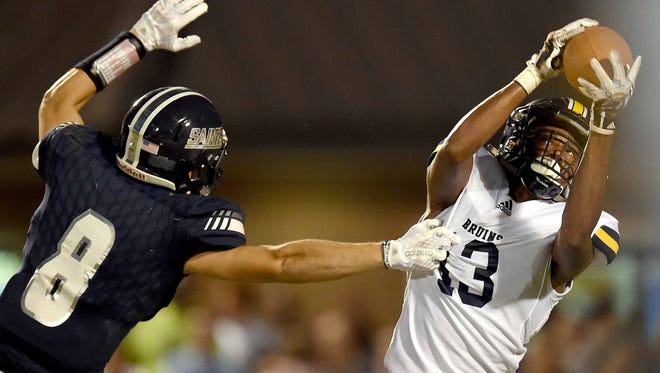 St. Joseph's Trey Frierson (13) grabs his second of two interceptions against St. Andrew's  in the first half as Saints receiver Nathan Barham (8) tries to tackle him on Friday, September 8, 2017, at St. Andrew's Episcopal School in Ridgeland, Miss.