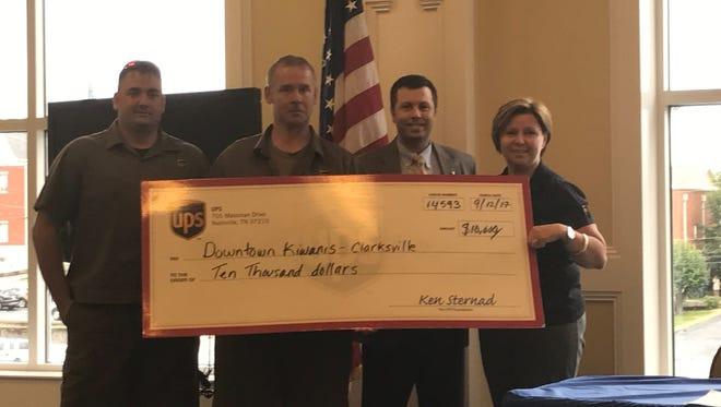 Downtown Kiwanis Club President Daniel Binkley and Board member Bo Kitchen receive grant check from members of Clarksville UPS.
