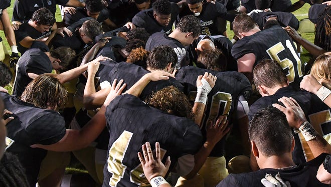 Players and coaches pray after the game with Powdersville High School, on Cunningham Field in Pendleton on Friday.
