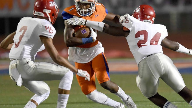 Madison Central's Cameron White (1) looks to get by Warren Central's Kevius McDaniel (24) and Caleb Wilson (3) on Friday, October 6, 2017, at Madison Central High School in Madison, Miss.