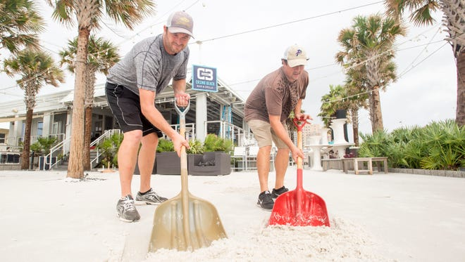 Owner Matt LaFon, left, and executive chef Shane Bourke start to shovel drifted sand on the deck at the Casino Beach Bar and Grill after Hurricane Nate in Pensacola on Sunday, October 8, 2017.