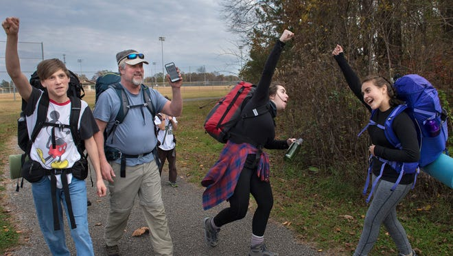 """Zachary Parkerson, 14, Kailey McKee, 18, and Abby Foster, 13, raise their fists in celebration as hike leader David Parkerson notifies them that they have walked exactly one mile Friday, Nov. 17, 2017, during HomeLife Academy's North Park Wilderness Adventure in Jackson. """"There's so much that kids miss out of when they just sit inside,"""" said David, the founder and president of HomeLife Academy. """"So being outdoors connects them to God's creation, to each other and to teamwork."""""""